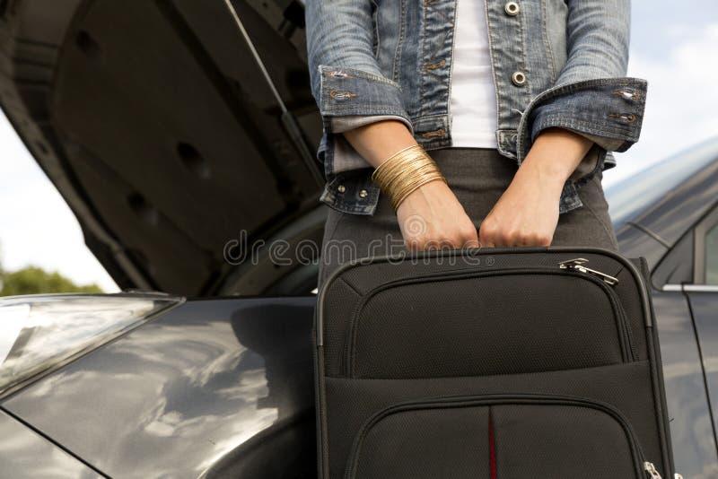 Jeune femme avec la valise à côté de la voiture cassée prête à la laisser photo stock