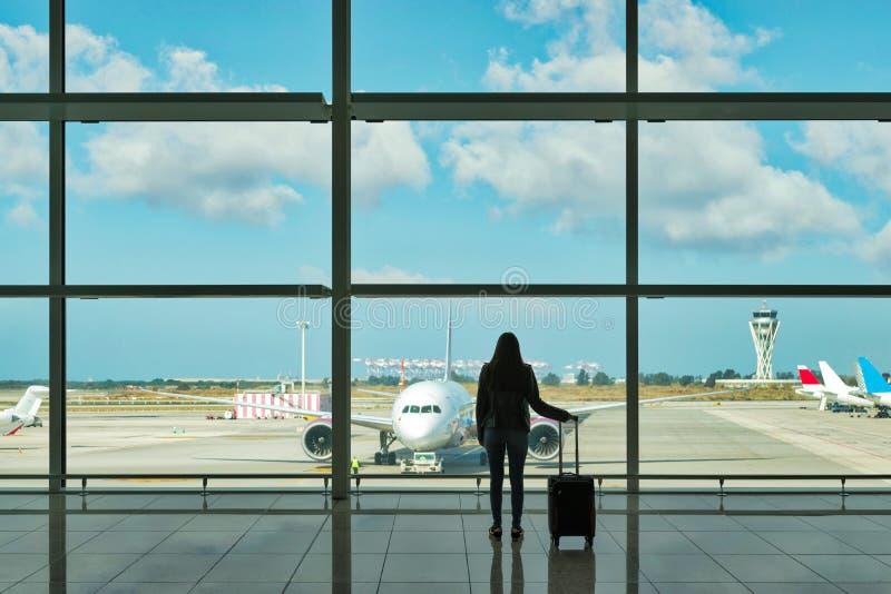 Jeune femme avec la valise dans le hall de départ à l'aéroport concept de course images stock