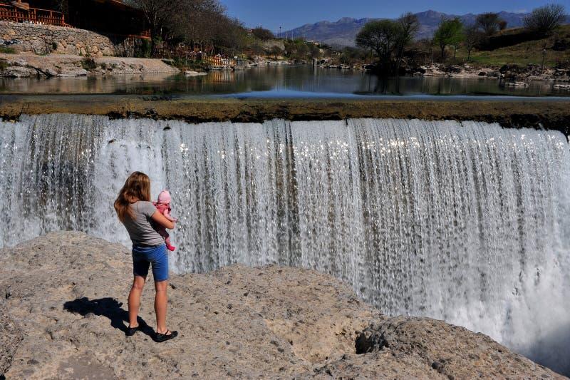 Jeune femme avec le bébé à la cascade photographie stock