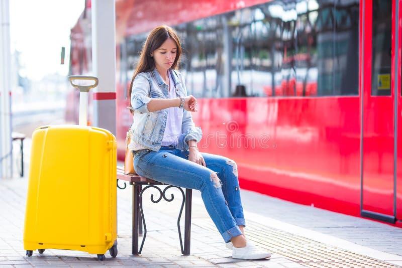Jeune femme avec le bagage sur l'attente de plate-forme de train photographie stock libre de droits