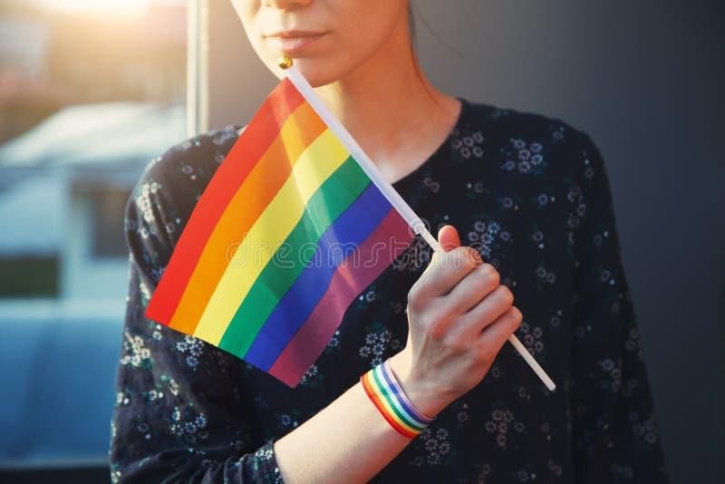 Jeune femme avec le bracelet de ruban d'arc-en-ciel sur sa main tenant le drapeau coloré d'arc-en-ciel de lgbt image stock