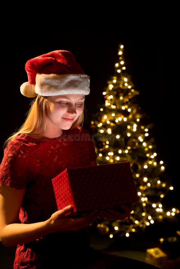 Jeune femme avec le cadeau, l'arbre de Noël et le fond décoratif de bokeh d'éclairage Elf et sapin avec des décorations images libres de droits