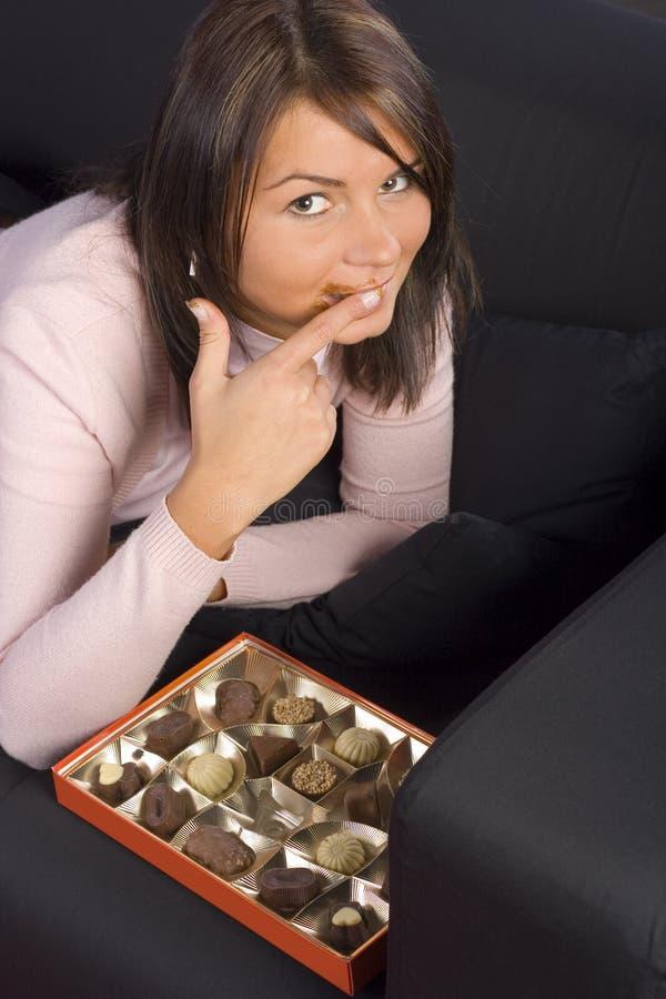 Jeune femme avec le cadre de chocolats photographie stock