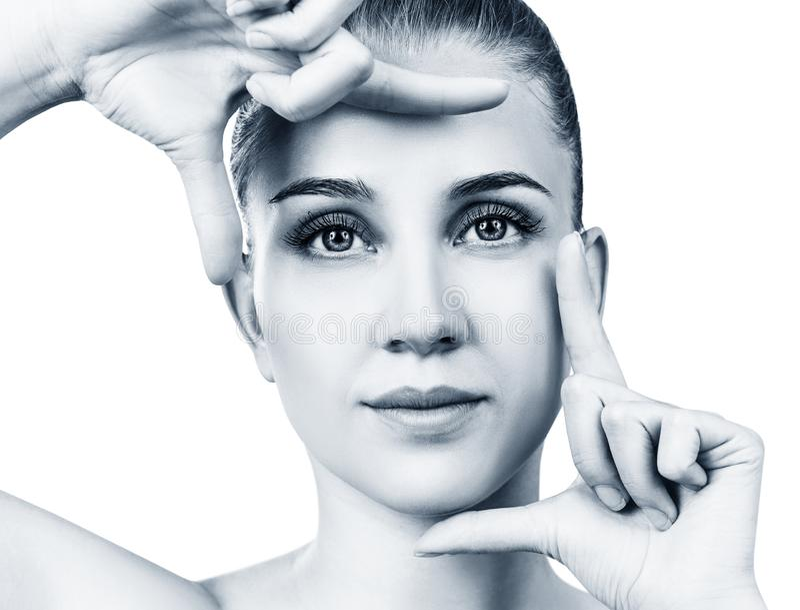 Jeune femme avec le cadre parfait de mains d'expositions de peau au-dessus du visage photos libres de droits