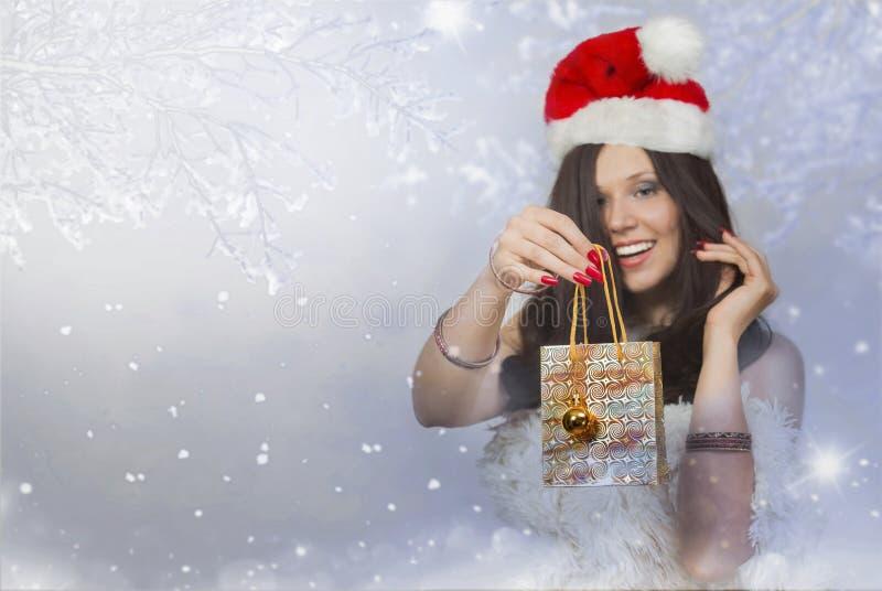 Jeune femme avec le chapeau de Noël donnant le cadeau avec le jouet de Noël photo libre de droits