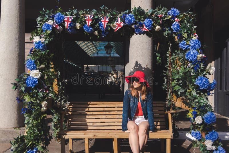 Jeune femme avec le chapeau rouge posé sur un banc de oscillation à Londres image stock
