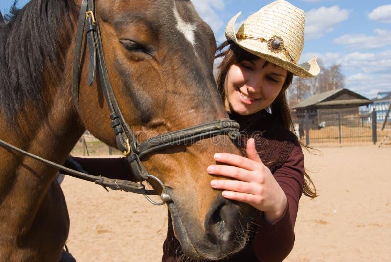 Jeune femme avec le cheval dans le village images stock