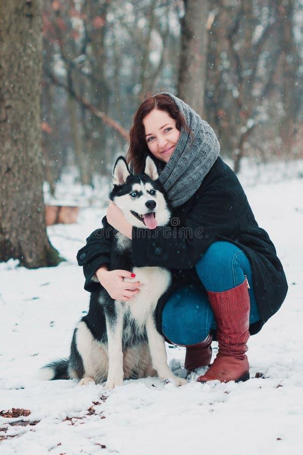 Jeune femme avec le chien enroué en parc d'hiver images stock