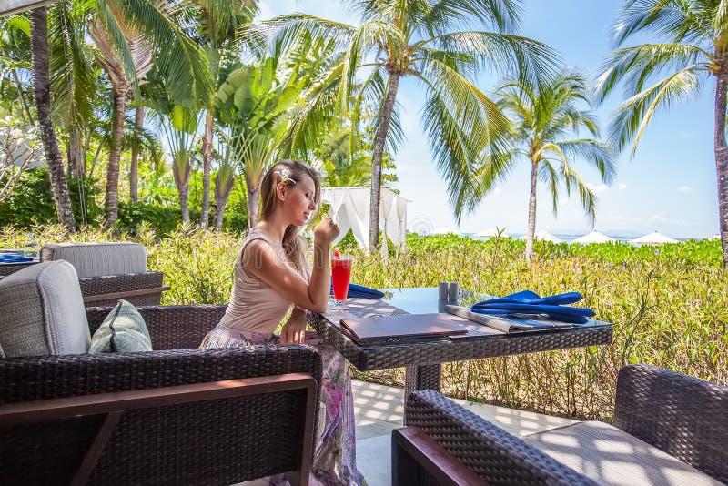 Jeune femme avec le coctail se reposant dans le restaurant extérieur images stock