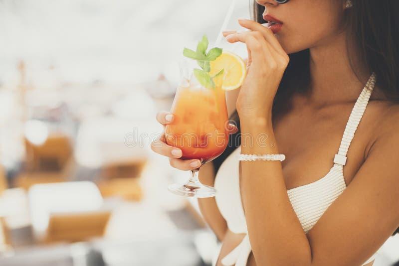 Jeune femme avec le coctail sur la plage à l'été photos stock