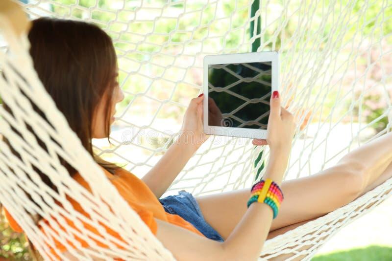 Jeune femme avec le comprimé détendant dans l'hamac dehors image libre de droits