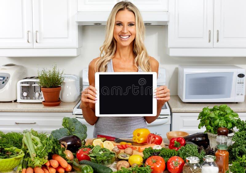 Jeune femme avec le comprimé dans la cuisine photo stock