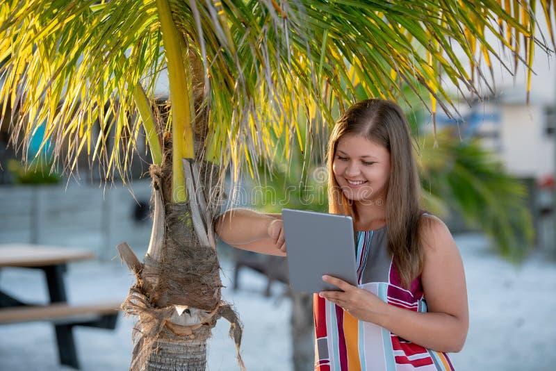 Jeune femme avec le comprim? sur la plage photos stock