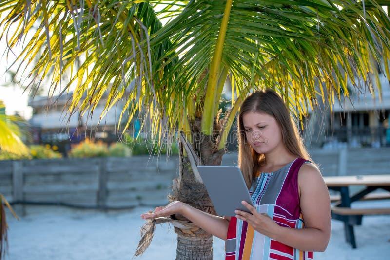 Jeune femme avec le comprim? sur la plage images libres de droits