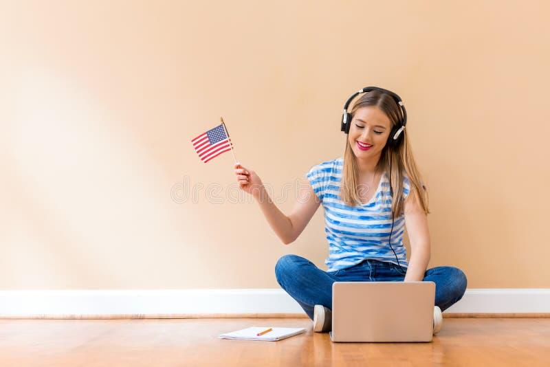 Jeune femme avec le drapeau des Etats-Unis utilisant un ordinateur portable photo libre de droits
