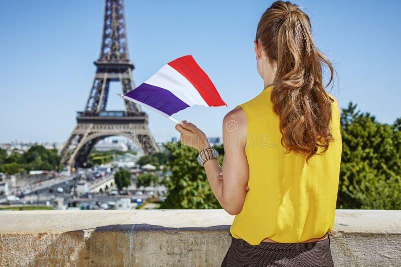 Jeune femme avec le drapeau français contre Tour Eiffel à Paris photographie stock libre de droits