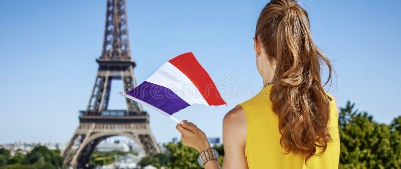 Jeune femme avec le drapeau français contre Tour Eiffel à Paris photographie stock
