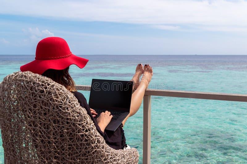 Jeune femme avec le fonctionnement rouge de chapeau sur un ordinateur dans une destination tropicale image libre de droits