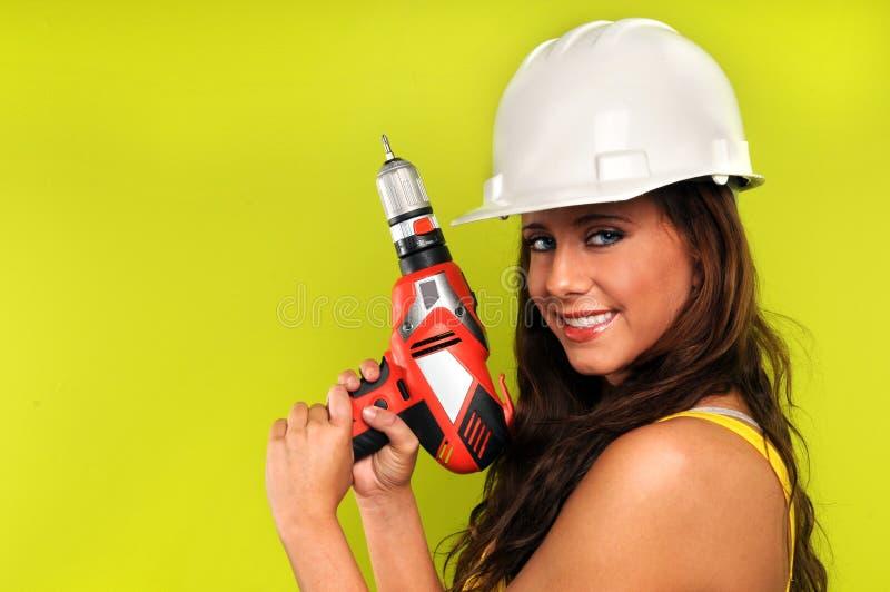 Jeune femme avec le foret sans fil photo stock