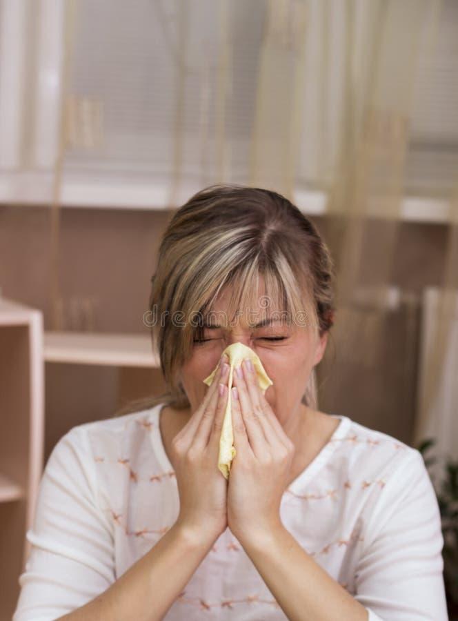 Jeune femme avec le froid soufflant son écoulement nasal photo libre de droits