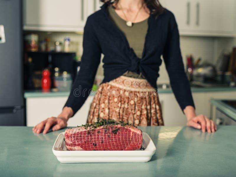 Jeune femme avec le joint de torréfaction dans la cuisine photos stock