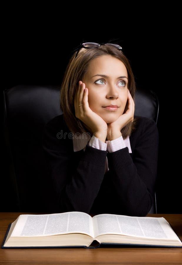 Jeune femme avec le livre au bureau photographie stock libre de droits