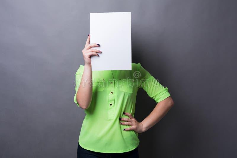 Jeune femme avec le livre blanc vide au visage photographie stock libre de droits