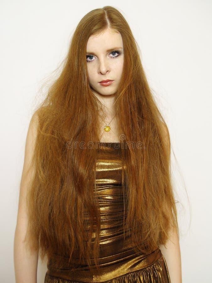 Jeune femme avec le long cheveu rouge dans la robe photographie stock libre de droits