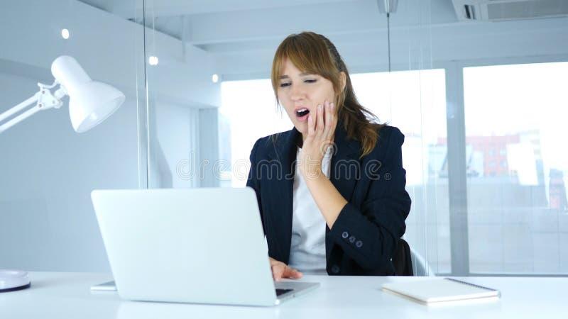 Jeune femme avec le mal de dents dans le bureau, douleur dans des dents photos libres de droits