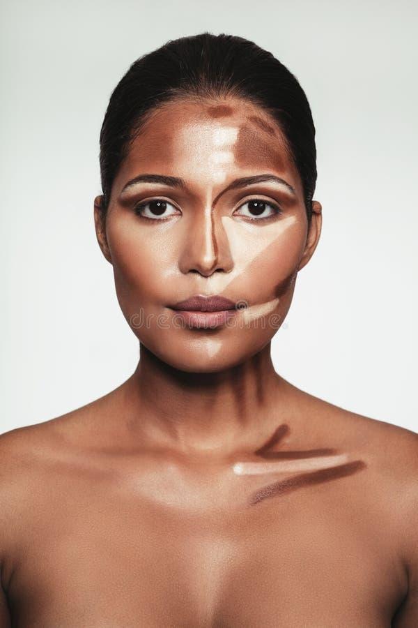 Jeune femme avec le maquillage de découpe et de point culminant sur le visage photo libre de droits