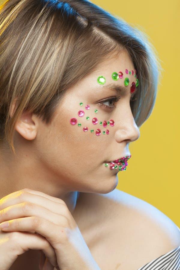 Jeune femme avec le maquillage de vacances sur son visage images stock