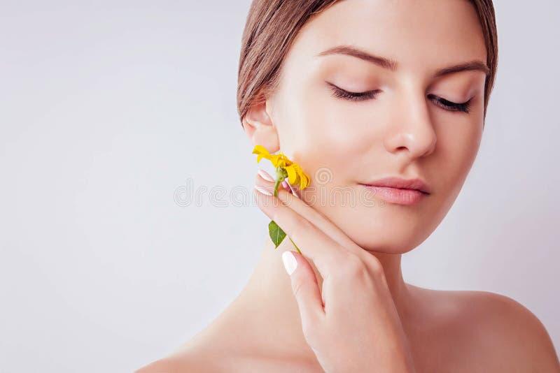 Jeune femme avec le maquillage naturel tenant une fleur Concept organique de cosmétiques photos stock