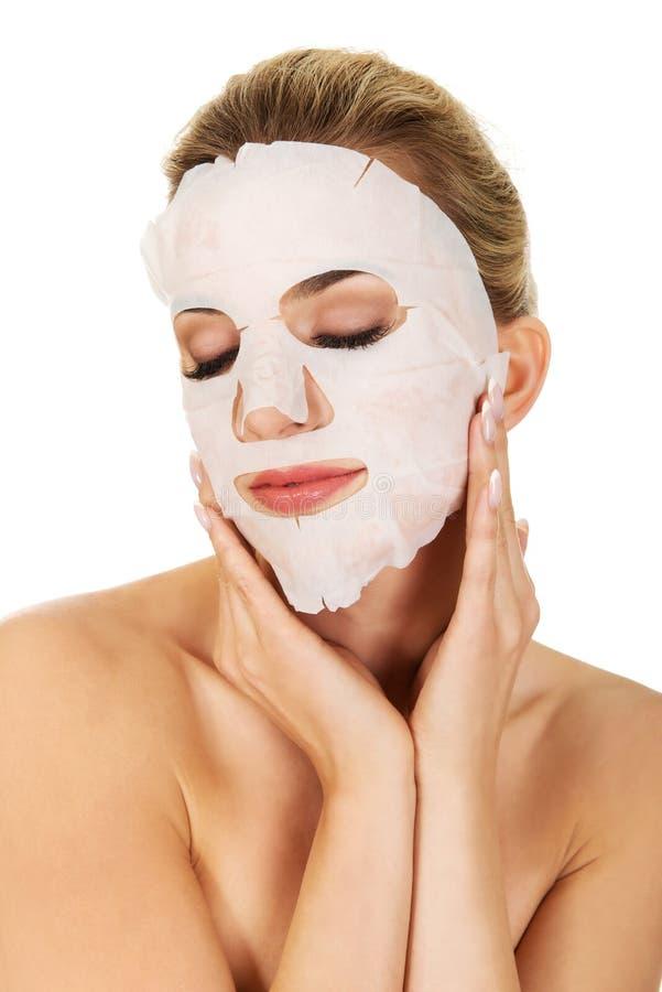 Jeune femme avec le masque facial images stock