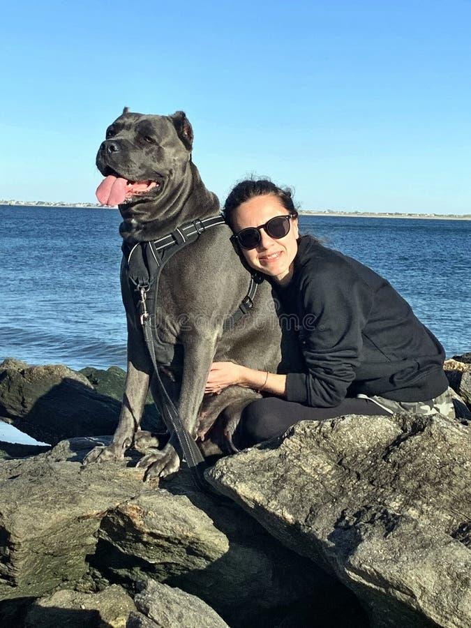 Jeune femme avec le mastiff de corso de canne sur des pierres photographie stock libre de droits