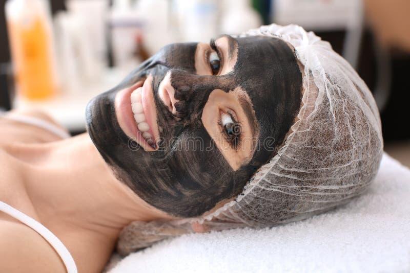 Jeune femme avec le nanogel de carbone sur son visage dans le salon photo stock
