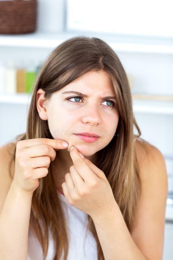 Jeune femme avec le nettoyage d'irritation de peau son visage images stock