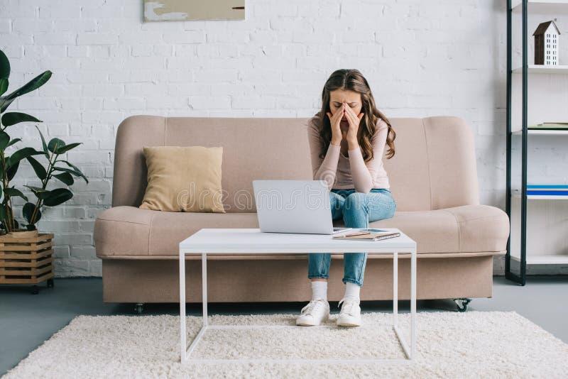 jeune femme avec le pont de nez de frottage de mal de tête tout en travaillant avec l'ordinateur portable photo stock
