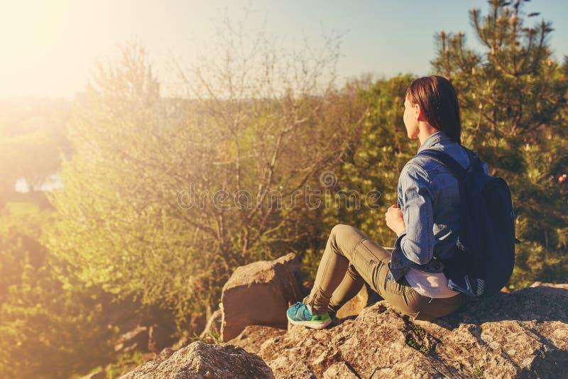 Jeune femme avec le sac à dos se reposant sur la falaise photo stock