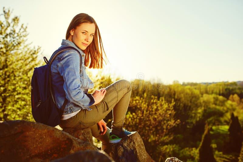 Jeune femme avec le sac à dos se reposant sur la falaise photographie stock libre de droits