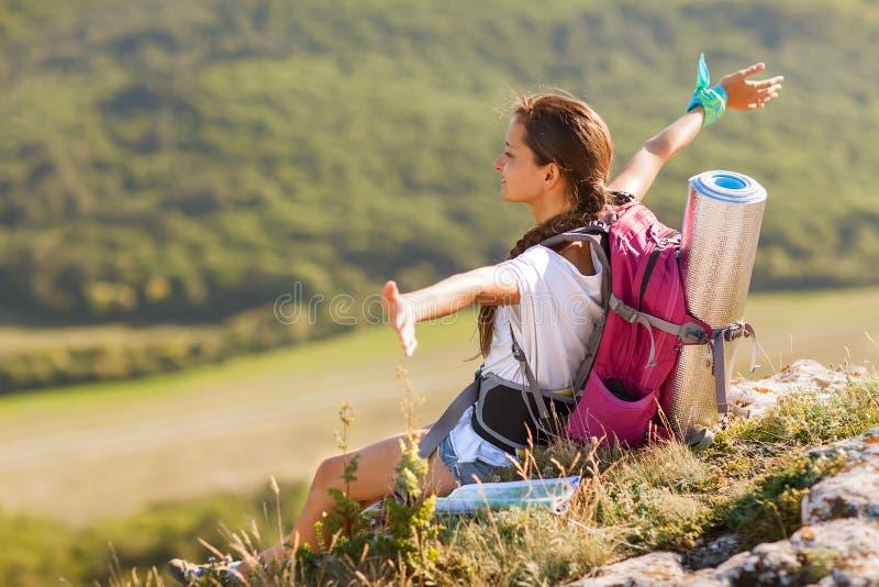 Jeune femme avec le sac à dos se reposant sur le bord de la falaise image libre de droits