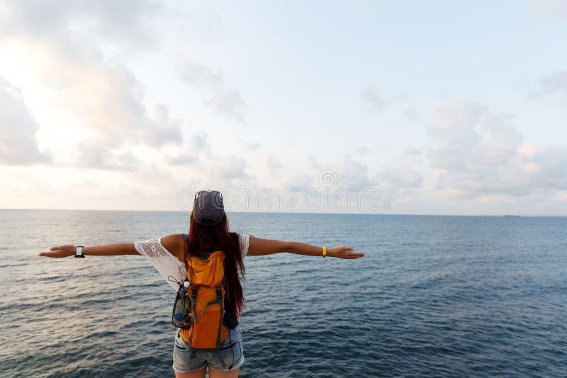 Jeune femme avec le sac à dos sur la falaise appréciant la mer et le coucher du soleil photo libre de droits