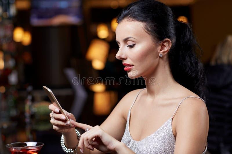 Jeune femme avec le smartphone à la boîte de nuit ou à la barre images libres de droits