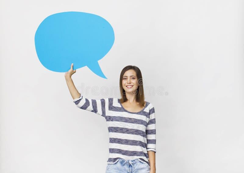 Jeune femme avec le sourire tenant la bulle bleue vide de la parole sur le fond blanc photo libre de droits