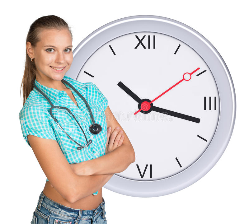 Jeune femme avec le stéthoscope et l'horloge image libre de droits