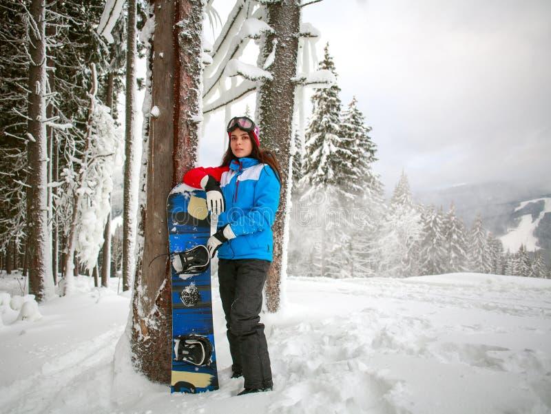 Jeune femme avec le surf des neiges dans la forêt neigeuse d'hiver sur la montagne photos libres de droits