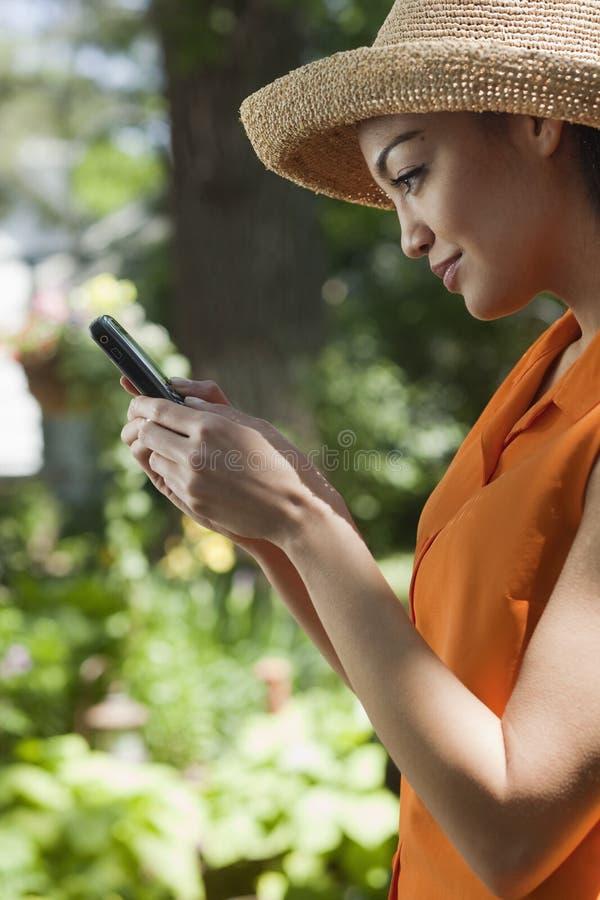 Jeune femme avec le téléphone portable dans le jardin photographie stock