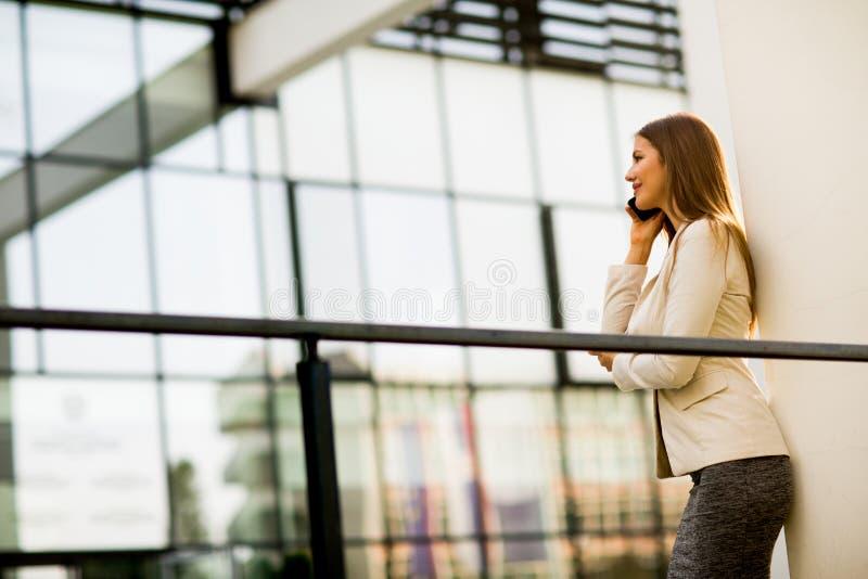 Jeune femme avec le téléphone portable devant l'immeuble de bureaux photo stock