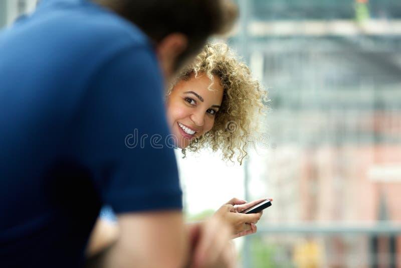 Jeune femme avec le téléphone portable regardant l'homme images stock