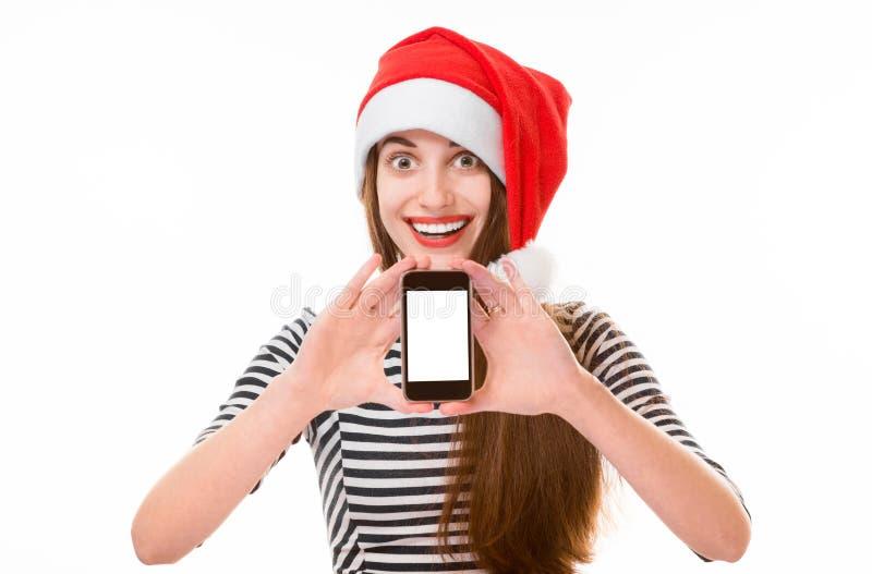 Jeune femme avec le téléphone portable sur Noël photographie stock