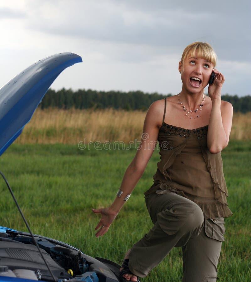 Jeune femme avec le véhicule cassé. photos libres de droits
